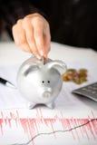 Женская рука кладя монетку в копилку на столе офиса стоковая фотография rf
