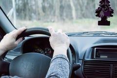 Женская рука на приводных колесах Управлять современным концом-вверх рулевого колеса и руки автомобиля Стоковая Фотография RF