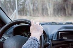 Женская рука на приводных колесах Управлять современным концом-вверх рулевого колеса и руки автомобиля Стоковое Фото