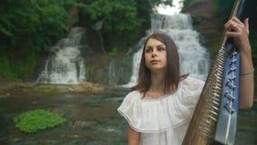 Женская рука нежно касается строкам bandura на водопаде сток-видео