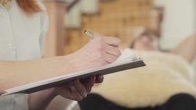 Женская рука неузнаваемого психолога пишет что-то вниз в тетради или в терпеливой карте Молодой парень на a акции видеоматериалы