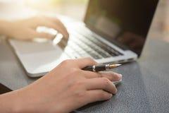 Женская рука печатая на клавиатуре пока сидящ на ее работая plac Стоковые Фото