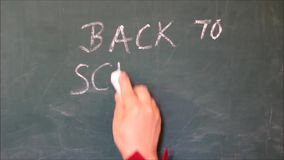 Женская рука писать текст назад к школе на доске и рисуя smiley под словами видеоматериал
