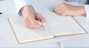 Женская рука пишет с ручкой в тетради дневника Стоковая Фотография