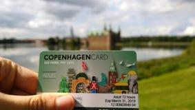 Женская рука показывает туристскую карточку Копенгагена в пригороде Hillerod на заднем плане замка Frederiksborg стоковые фотографии rf