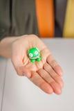Женская рука показывая малого зеленого изверга пластилина Стоковые Изображения RF