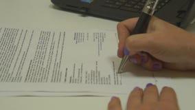 Женская рука подписывая бумагу контракта