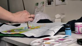 Женская рука прикладывает голубую краску на ткани с картиной с щеткой На переднем плане палитра с красками и ванной бесплатная иллюстрация