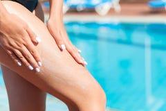 Женская рука прикладывая сливк солнцезащитного крема на ее ноге бассейном Фактор предохранения от Солнца в каникулах, концепции стоковое фото
