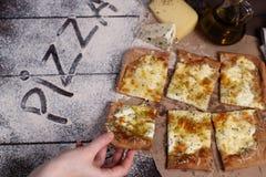 Женская рука принимает кусок сыра пиццы 4 с душицей и оливковым маслом fromaggi quattro стоковое изображение rf