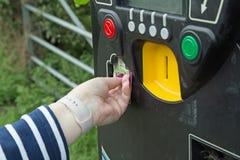 Женская рука принимая билет от автопарковочного счетчика стоковые фото