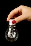 Женская рука при электрическая лампочка изолированная на черной предпосылке Стоковая Фотография RF