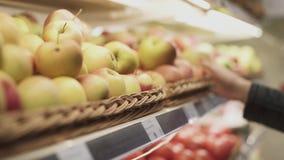 Женская рука продолжает полку с яблоками и выбирает яблоко сток-видео