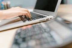 Женская рука работая на компьтер-книжке Стоковые Фото