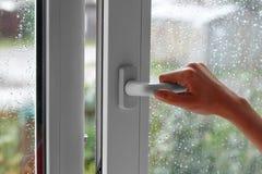Женская рука раскрывает окно с падениями воды Закрывает окно Стоковое Изображение