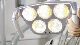 Женская рука регулируя зубоврачебное освещение СИД перед деятельностью, инструментами дантиста и профессиональным получать оборуд сток-видео