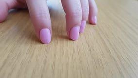 Женская рука с белой кожей и розовыми короткими ногтями царапая деревянный стол видеоматериал