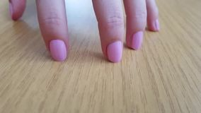 Женская рука с белой кожей и розовыми короткими ногтями царапая деревянный стол акции видеоматериалы