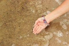 Женская рука с браслетом в форме крупного плана seashells зачерпнула вверх пузыри морской воды Стоковое Изображение RF