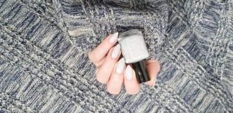 Женская рука с ногтями белого света длинными и бутылкой стоковая фотография