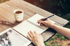 Женская рука с сочинительством карандаша на тетради Рука женщины с ручкой Стоковое фото RF