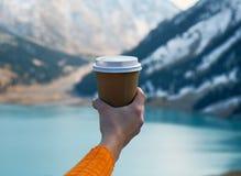 Женская рука с чашкой кофе на предпосылке озера горы Стоковое Изображение RF