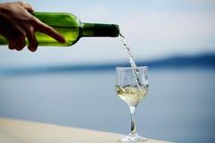 Женская рука льет вино Стоковые Изображения RF