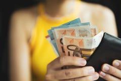 Женская рука piking вверх или подсчитывая деньги в бумажнике Стоковые Изображения