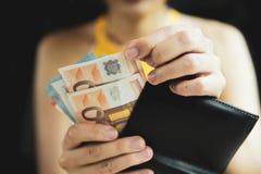 Женская рука piking вверх или подсчитывая деньги в бумажнике Стоковые Фотографии RF