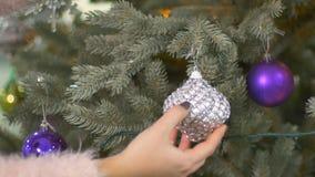 Женская рука ` s положила игрушку рождества на рождественскую елку видеоматериал