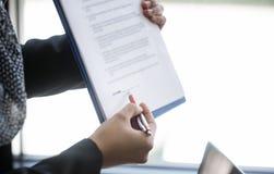 Женская ручка удерживания руки указывая на бумагу документа для знака cont Стоковые Фотографии RF