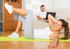 Женская тренировка на циновке и инертном отдыхать парня Стоковые Изображения RF