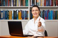 Женская улыбка доктора thumbs вверх Стоковые Изображения