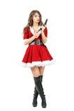 Женская шпионка замаскированная как личное огнестрельное оружие Санта Клауса перезаряжая смотря камеру Стоковое Изображение