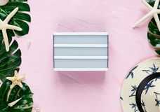 Женские аксессуары на розовой предпосылке с белой стильной шляпой моды, раковины путешественника, троповые листья monstera, морск стоковое изображение rf
