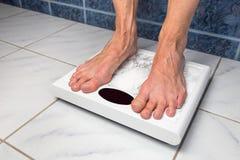 Женские босые ноги на масштабах ванной комнаты стоковая фотография rf