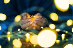 Женские гирлянды владением рук светов Стоковые Фото