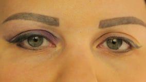 Женские глаза один глаз покрашенный с темными пурпурными тенями видеоматериал