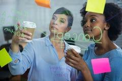 Женские график-дизайнеры с устранимым чтением чашки отправляют СМС на стекле Стоковое Изображение RF