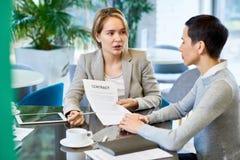 Женские деловые партнеры обсуждая контракт Стоковое Фото
