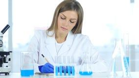 Женские детали сочинительства ученого, результат исследования в лаборатории Стоковое Изображение RF