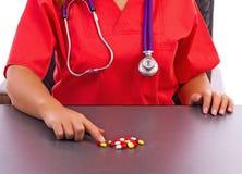 Женские доктор или нюна указывая пилюльки на таблице Стоковая Фотография