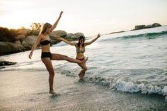Женские друзья имея потеху на пляже Стоковые Фотографии RF