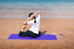 Женские друзья практикуя йогу на пляже стоковые фотографии rf