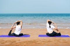 Женские друзья практикуя йогу на пляже стоковые изображения