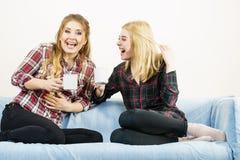 Женские друзья сидя на софе имея потеху Стоковые Изображения
