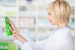 Женские детали продукта чтения аптекаря в фармации Стоковое Изображение