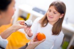 Женские диетолог доктора и пациент девушки Доктор держа апельсин и торт Стоковые Фото