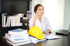 Женские инженеры думают для того чтобы создать новые работы и усмехаются стоковое фото rf
