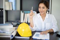 Женские инженеры думают для того чтобы создать новые работы и усмехаются стоковая фотография rf